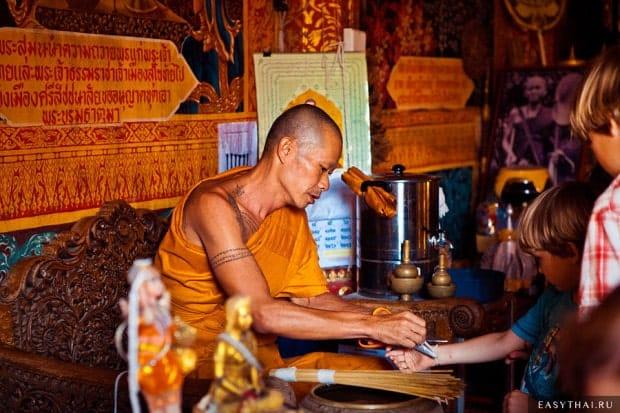 Буддийский монах завязывает веревочку на удачу