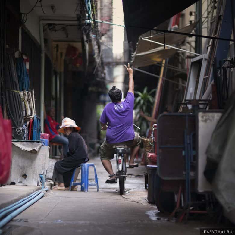 Мужчина на велосипеде в улочке Бангкока