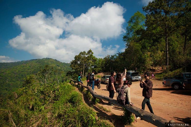 Туристы фотографируются на фоне гор